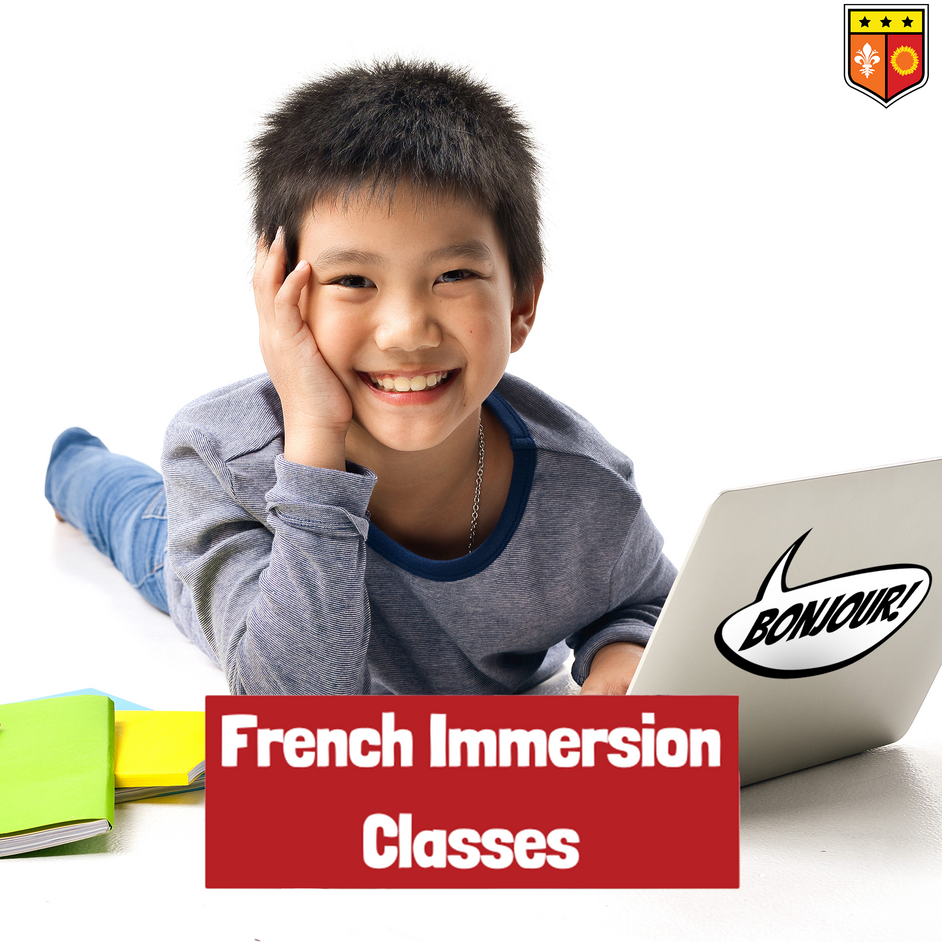 French Immersion classes. Pictured is a smiling young boy in front of a laptop.