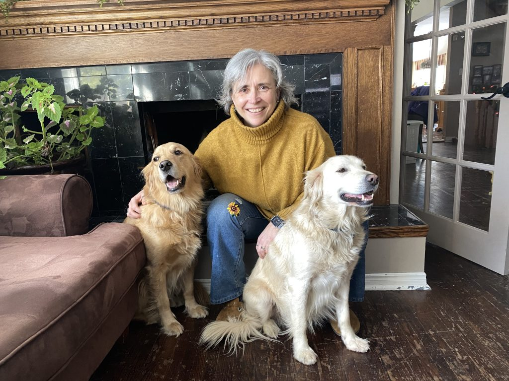 Martine in a yellow sweater crouching with her two golden retrievers, Alice and Penny.